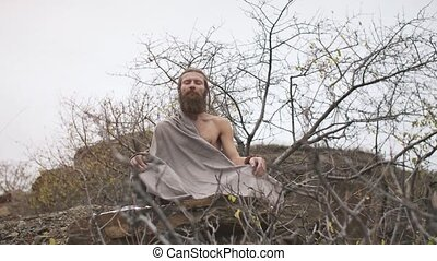 Ascetic yogi sitting in meditation on the rock