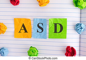ASD (Autism spectrum disorder) on notebook sheet with some colorful crumpled paper balls around it