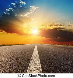 asfaltroad, under, solnedgång med skyar