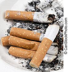 ashtray full of cigarettes on white