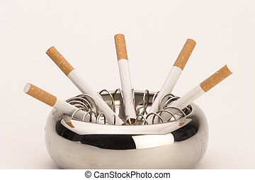 Ashtray with cigarettes - An ashtray with cigarettes against...