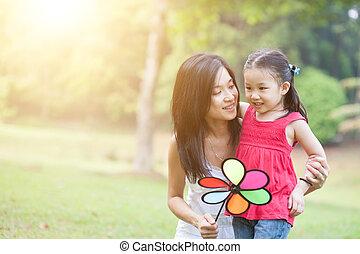 asiático, madre e hija, juego, molino de viento, en, el, verde, park.