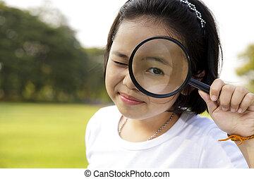 asiático, menininha, segurando, um, lupa, em, ao ar livre