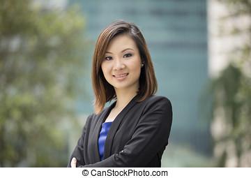 asiático, mujer de negocios que está de pie, exterior.