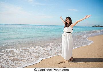 asiático, mulher grávida, desfrutando, em, a, praia, com, braços abertos