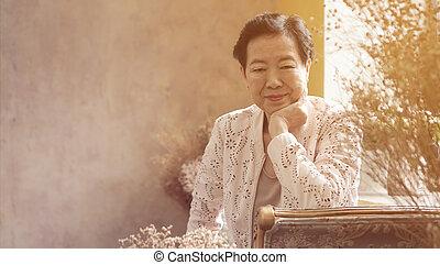 asiático, mulher idosa, sentar, em, bonito, luxo, interior, sala, tuscan, vindima, estilo