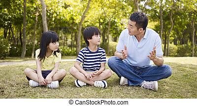 asiático, padre y niños, hablar, en el estacionamiento