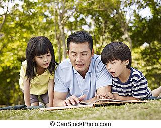 asiático, padre y niños, libro de lectura, juntos