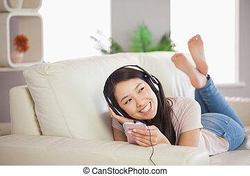 asiático, smartphone, hogar, música, niña, habitación, sofá, sonriente, acostado, escuchar, sentado