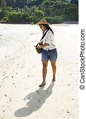 asiático, tailandés, el caminar de la mujer, en la playa, en, el, andaman, océano, mientras, agua de mar, nivel, decreased