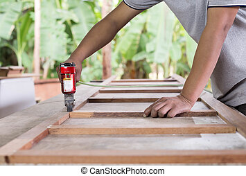 Asia carpenter use air-gun for make a furniture