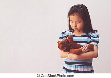asia girl hugging a teddy bear