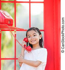 asia girl in red in a public phone
