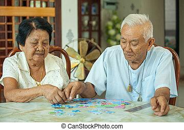 asian összekapcsol, idősebb ember, játék, noha, egy, kirakós játék, otthon