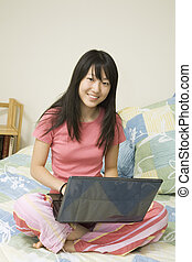 Asian American teen working on laptop computer
