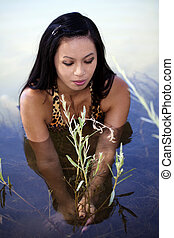 Asian American Woman In River Holding Plant