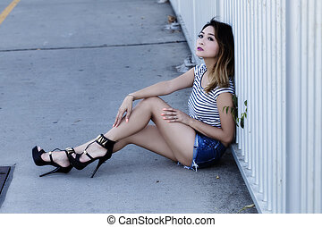 Asian American Woman Sitting In Jean Shorts And Top