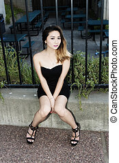 Asian American Woman Sitting On Cement Curb