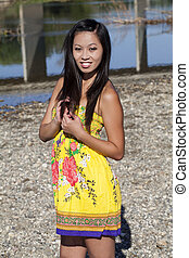 Asian American Woman Standing Outdoors Yellow Dress