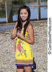 Asian American Woman Standing Outdoors Yellow Dress