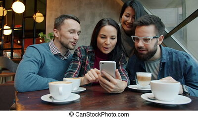 Asian and Caucasian friends using smartphone talking smiling having fun in cafe