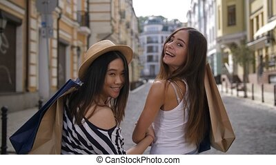 Asian and caucasian shopper friends smiling at cam -...