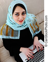 Asian Arabic young with laptop on sofa