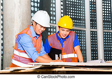 Asian architect and supervisor on building site