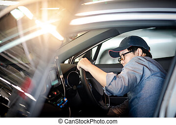 Asian auto mechanic checking inside of the car