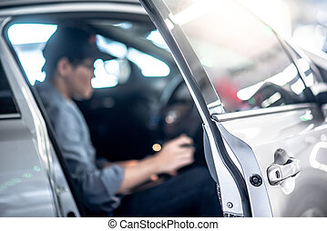 Asian auto mechanic sitting inside of the car