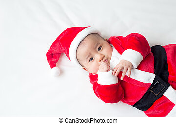 Asian baby boy in Santa Claus dress on white bed for Christmas day and Happy new year festival