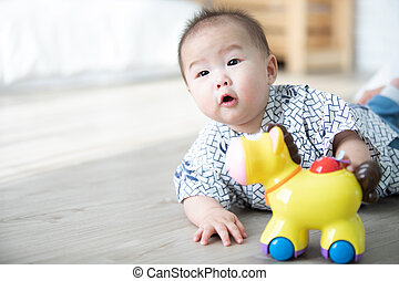 Asian baby boy playing hourse toys on the floor.