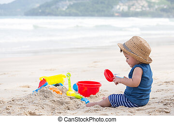 Asian baby boy playing sand on the beach, Baby 1 year old
