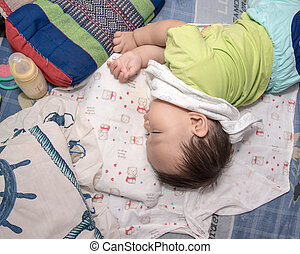 Asian baby boy sleeping on the bed , his right hand holding  milk bottle, Top view photo