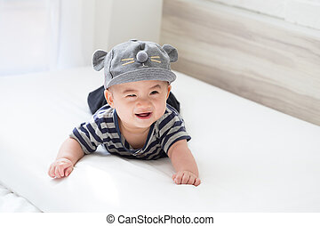 Asian baby boy smiling and relaxing in white bedroom
