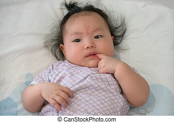 Asian baby gril. - Four month old baby girl, lying on a bed.