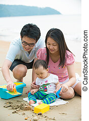 asian baby playing sand on the beach with father and mother