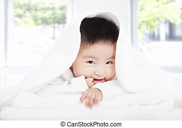 asian baby sucking  finger under  blanket or towel
