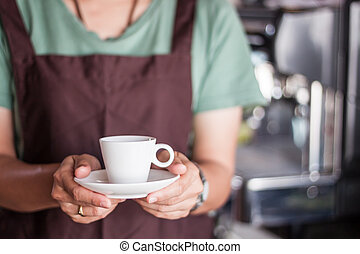 Asian barista serving freshly brewed coffee, stock photo