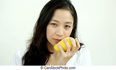 Asian beautiful woman eating posing with mango. Summer delight tropical fruit.