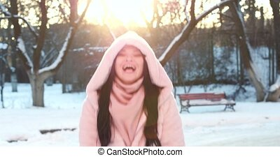 Asian blowing snow in the palms and having fun. - Asian...
