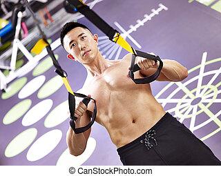 asian body builder exercising in gym