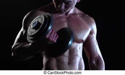 Asian bodybuilder training biceps with a dumbbells. Black...