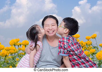 boy and girl kissing their mother in park