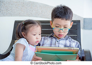 Asian boy and girl playing games on tablet computer