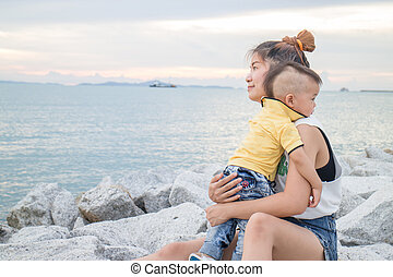 Asian boy chilling with his mother on seaside