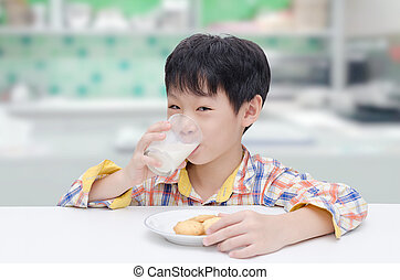 boy eating cookies with milk in kitchen