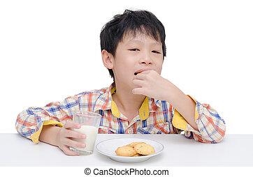 boy eating cookies with milk
