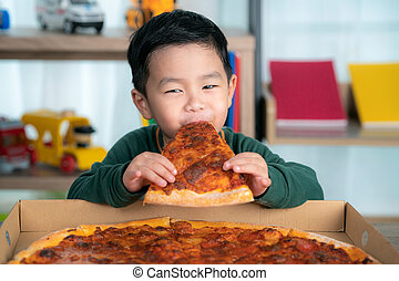 Asian boy eating pizza