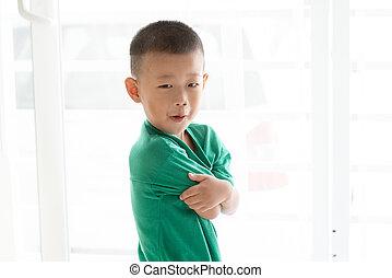 Asian boy grimacing